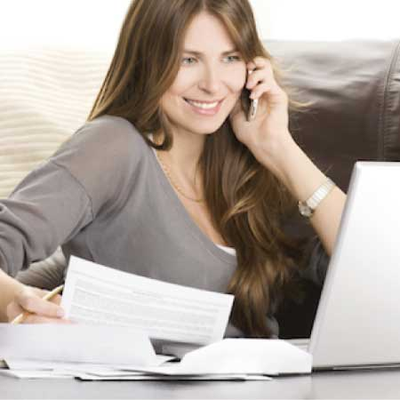 Glad kvinna ansöker om att låna pengar via dator